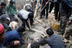 epa04719892 People try to free a man from the rubble of a destroyed building after an earthquake hit Nepal, in Kathmandu, Nepal, 25 April 2015. A 7.9-magnitude earthquake rocked Nepal destroying buildings in Kathmandu and surrounding areas, with unconfirmed rumours of casualties. The epicentre was 80 kilometres north-west of Kathmandu, United States Geological Survey. Strong tremors were also felt in large areas of northern and eastern India and Bangladesh.  EPA/NARENDRA SHRESTHA